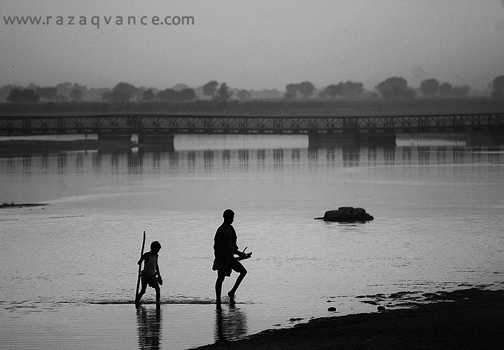 FATHER AND SON CROSSING THE RIVER RAVI IN A MISTY EVENING