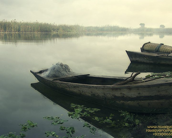 Parked Boats on a Lake in a Cloudy Mystic Morning.