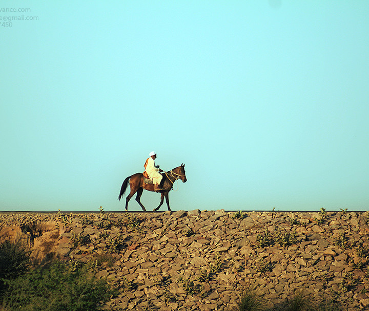 A Lone Horse Rider Is Travelling Over The Bank Of River Ravi